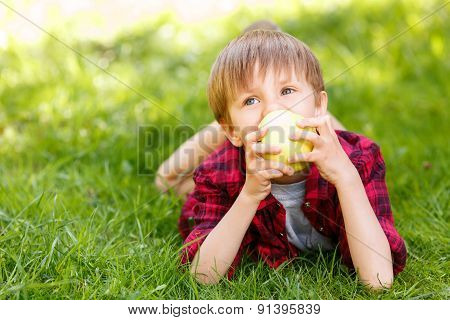 Little boy lying on grass with apple