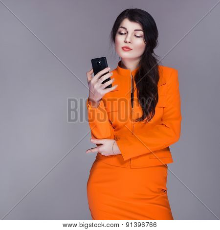 Beautiful Brunette Caucasian Woman In Orange Stylish Buisness Suit Typing Message On The Phone. Grey
