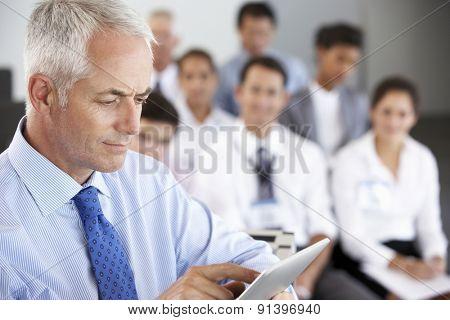Middle Aged Businessman Delivering Presentation At Conference