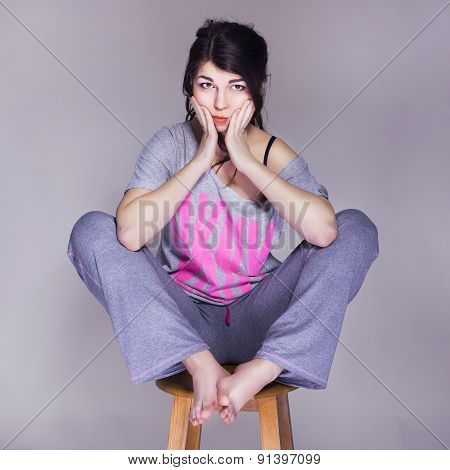 Brunette Beautiful Woman Sitting On A Chair Home Alone, Happy. Neutral Grey Background