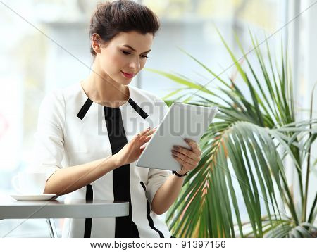 Pensive Businesswoman Reading An Article On Tablet Computer In A Cafe