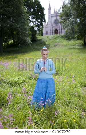 The beautiful young woman in a blue dress in the field
