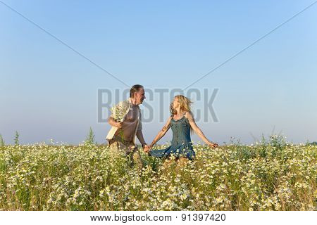 The happy young pair in the field of chamomiles jumps