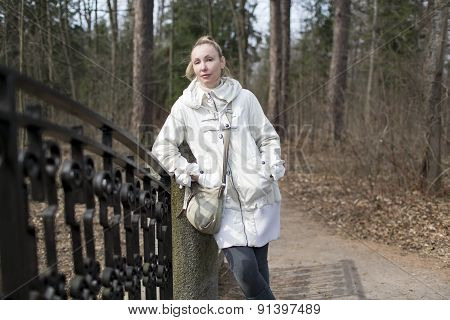 the young woman on the bridge in park in the early spring