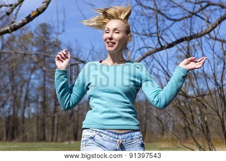 The woman jumps in the early spring wood