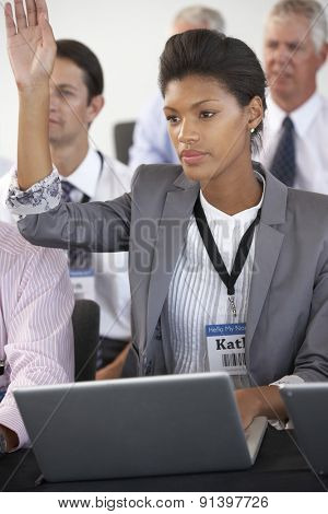 Female Delegate Listening To Presentation At Conference Making Notes On Laptop