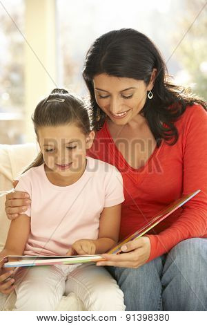 Mother And Daughter Playing Reading Book At Home
