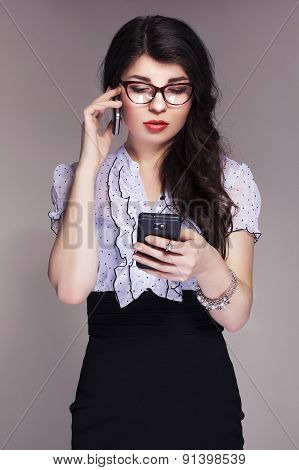Beautiful Brunette Caucasian Business Woman In Classic Dress And Glasses Looks Like Teacher Working