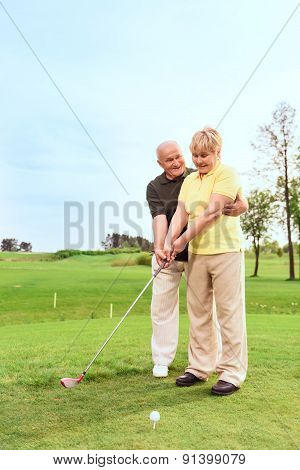 Old man teaching his wife to play golf