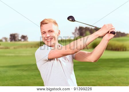 Young handsome man driving ball towards