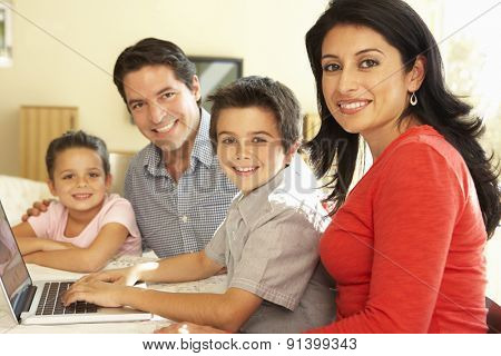 Young Hispanic Family Using Computer At Home