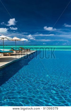 Infinity swimming pool on the beach of tropical island with white beach umbrellas and chairs