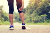 picture of jogger  - young fitness woman jogger hold her sports injured leg at forest trail - JPG