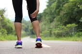 stock photo of jogger  - young fitness woman jogger hold her sports injured leg at forest trail - JPG