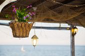picture of hook  - Beautiful hanging basket with artificial flowers hooked on a wooden shelter on the sea shore against a nice blurred sea - JPG