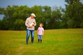 image of grandfather  - grandfather and grandson walking through the green field with puppy in hands - JPG