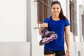 stock photo of inline skating  - Portrait of a pretty young woman in sporty outfit carrying her inline skates from her shoulder - JPG