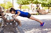 stock photo of bench  - Profile view of a young woman doing push ups on a park bench - JPG