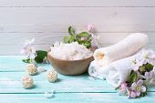 picture of salt-bowl  - Spa or wellness setting. Sea salt in bowl towels and apple blossom on turquoise wooden background against whit wall . Selective focus is on salt. ** Note: Shallow depth of field - JPG