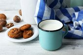 foto of caw  - Milk in mug with walnuts and cookies on wooden background - JPG