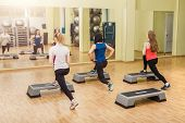 image of step aerobics  - Group of young sportive women making step aerobics in the fitness class  - JPG
