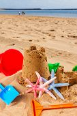 image of starfish  - sand castle  with plastic toys and starfish on the sunny summer  beach - JPG
