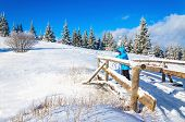 stock photo of covered bridge  - Beautiful winter landscape with staring woman standing on a snow - JPG