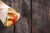 foto of sandwich wrap  - Tortilla chicken wrap sandwich on wooden background with blank space - JPG