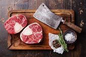 image of cut  - Raw fresh cross cut veal shank and seasonings for making Osso Buco on wooden cutting board with meat cleaver - JPG