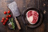 stock photo of veal  - Raw fresh cross cut veal shank for making Osso Buco and meat cleaver on dark wooden background - JPG