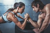 stock photo of wrestling  - Athlete muscular sportsmen man and woman with hands clasped arm wrestling challenge between a young couple Crossfit fitness sport training lifestyle bodybuilding concept - JPG
