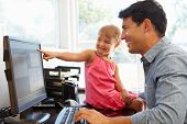 foto of father daughter  - Father working in home office with daughter - JPG