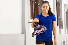pic of inline skating  - Portrait of a pretty young woman in sporty outfit carrying her inline skates from her shoulder - JPG