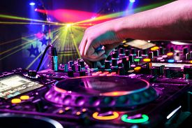 picture of track field  - Dj mixes the track in the nightclub at party. In the background laser light show ** Note: Shallow depth of field - JPG