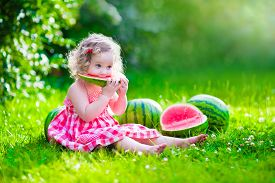 stock photo of eat grass  - Child eating watermelon in the garden - JPG