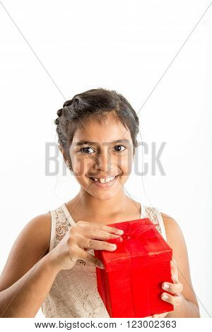 smiling young girl looks at camera as she begins to openlid on a red gift box