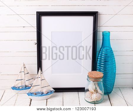 Black empty frame and ocean theme decorations on white wooden background. Place for text. Selective focus.