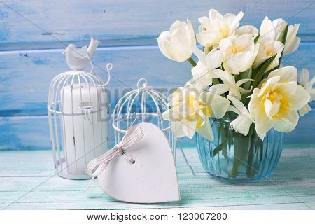 Bright white daffodils and tulips flowers in blue vase candles and white heart on turquoise painted wooden planks against blue wall. Selective focus.