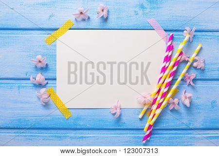 Bright pink and yellow paper straws tender flowers and empty tag for text on blue wooden background. Selective focus. Place for text.