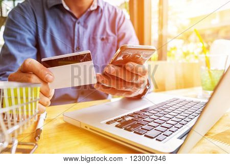 Man holding credit card in hand and entering security code using laptop keyboard.
