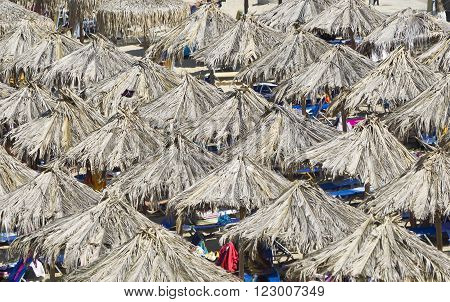 Beach with straw umbrellas in Greece Chalkidiki Sithonia.