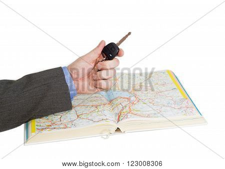 Male hand with car key over an open old road atlas on a light background