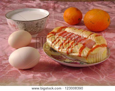 Healthy breakfast with hotdog bread milk egg and orange on crepe.