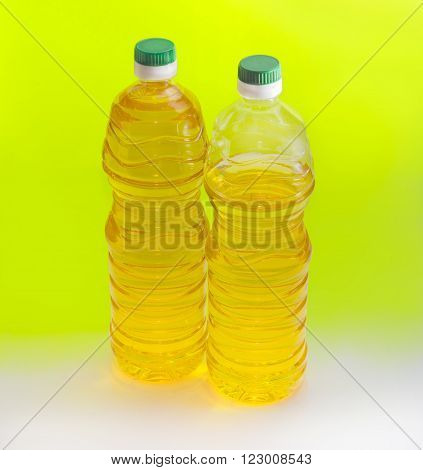 One full and one partially filled plastic bottle of unrefined sunflower oil on an yellow background