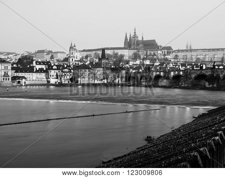 View of Prague Castle, Charles Bridge and Vltava River in early morning blue hour, Czech Republic. Black and white image.
