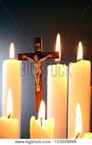 Small crucifix hanging on gray background among lighting candle