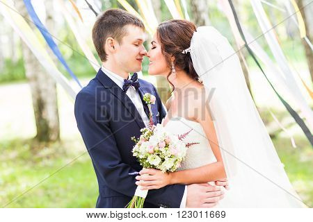 wedding couple hugging, the bride holding a bouquet of flowers in her hand, the groom embracing her.