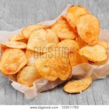 Homemade potato chips closeup on wooden texture