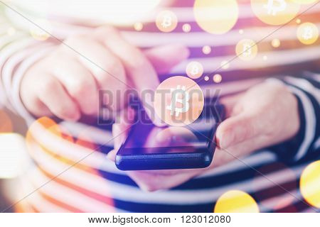 Woman paying with Bitcoins over smartphone close up of female hands using mobile phone device to complete online shopping transaction nice bokeh close up with selective focus and shallow depth of field.