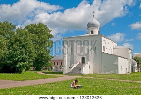 VELIKY NOVGOROD, RUSSIA - JULY 17, 2012: Girl draws near Church of Assumption of the Virgin on The Yaroslav's Court. Was built in 12 century.